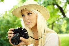 Smiling female with a camera Stock Photography