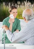 Smiling Female Caretaker Showing Ace Card To Royalty Free Stock Photo