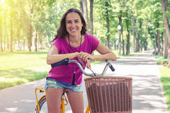 Smiling female in casual clothes posing on bicycle on the sunlit Stock Images