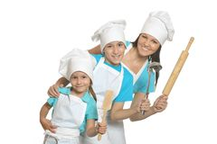 Smiling female chef with assistants. Isolated on white background stock image