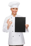 Smiling female chef with black blank paper Stock Photography