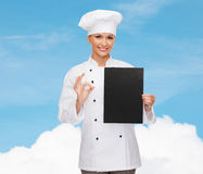 Smiling female chef with black blank paper Royalty Free Stock Photography