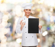 Smiling female chef with black blank paper Royalty Free Stock Photos