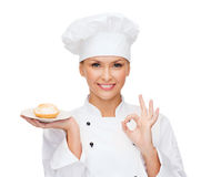 Smiling female chef with cake on plate Royalty Free Stock Images