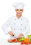 Smiling female chef chopping vagetables Royalty Free Stock Images
