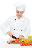 Smiling female chef chopping vagetables Stock Images
