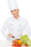 Smiling female chef chopping vagetables Royalty Free Stock Image