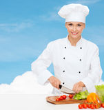 Smiling female chef chopping vegetables Royalty Free Stock Image
