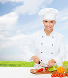 Smiling female chef chopping vegetables Stock Image