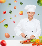 Smiling female chef chopping vegetables Stock Photography