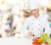 Smiling female chef chopping vegetables Stock Photo