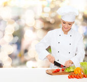 Smiling female chef chopping vegetables Royalty Free Stock Photos
