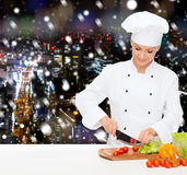 Smiling female chef chopping vegetables Royalty Free Stock Images