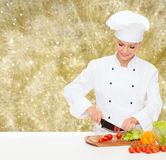 Smiling female chef chopping vegetables Stock Images