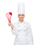 Smiling female chef with cooking equipment Royalty Free Stock Image