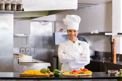 Smiling female chef with cut vegetables in kitchen. Portrait of a smiling young female chef standing with cut vegetables in the kitchen stock photos