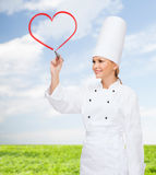 Smiling female chef drawing red heart on air Royalty Free Stock Images