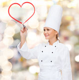 Smiling female chef drawing red heart on air. Cooking, new technology , advertisement and food concept - smiling female chef with marker drawing red heart on royalty free stock photos