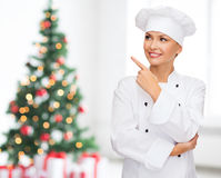 Smiling female chef dreaming  pointing finger up Stock Photography