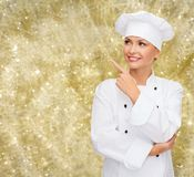 Smiling female chef dreaming pointing finger up Stock Image