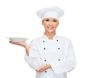 Smiling female chef with empty plate Royalty Free Stock Image