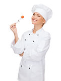 Smiling female chef with fork and tomato Stock Photography