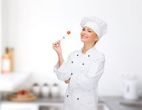 Smiling female chef with fork and tomato Stock Photo
