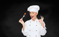 Smiling female chef with fork and tomato Stock Images