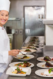 Smiling female chef garnishing food in kitchen Stock Photography