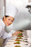 Smiling female chef garnishing food in kitchen Stock Image