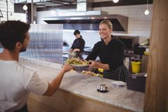 Smiling female chef giving fresh Greek salad to waiter. At coffee shop Royalty Free Stock Images