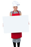 Smiling female chef holding an ad board Stock Image