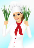 Smiling female chef holding green onion Royalty Free Stock Photo