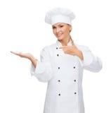 Smiling female chef holding something on hand Royalty Free Stock Photos