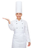 Smiling female chef holding something on hand Royalty Free Stock Photos