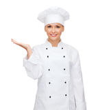 Smiling female chef holding something on hand Stock Images