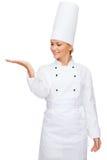 Smiling female chef holding something on hand Royalty Free Stock Image