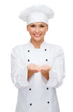 Smiling female chef holding something on hands Stock Photography