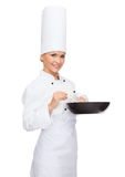 Smiling female chef with pan and spoon. Cooking and food concept - smiling female chef with pan and spoon stock images