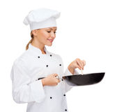 Smiling female chef with pan and spoon Royalty Free Stock Photography