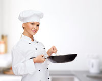 Smiling female chef with pan and spoon. Cooking and food concept - smiling female chef, cook or baker with pan and spoon stock images