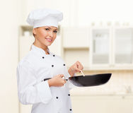 Smiling female chef with pan and spoon. Cooking and food concept - smiling female chef, cook or baker with pan and spoon stock photography