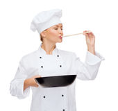 Smiling female chef with pan and spoon Stock Image