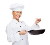 Smiling female chef with pan and spoon. Cooking and food concept - smiling female chef, cook or baker with pan and spoon tasting food stock image
