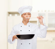 Smiling female chef with pan and spoon. Cooking and food concept - smiling female chef, cook or baker with pan and spoon tasting food stock photo