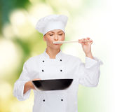 Smiling female chef with pan and spoon Royalty Free Stock Photo