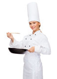 Smiling female chef with pan and spoon. Cooking and food concept - smiling female chef with pan and spoon tasting food royalty free stock photos