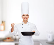 Smiling female chef with pan and spoon Royalty Free Stock Image