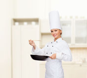 Smiling female chef with pan and spoon. Cooking and food concept - smiling female chef with pan and spoon tasting food royalty free stock images
