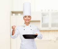 Smiling female chef with pan and spoon. Cooking and food concept - smiling female chef with pan and spoon tasting food stock photo